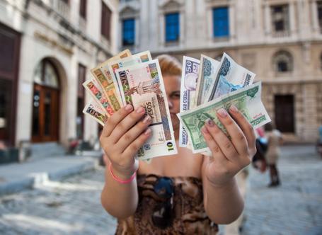 Cubana mostra na mão esquerda Pesos Cubanos, na direita CUCs.